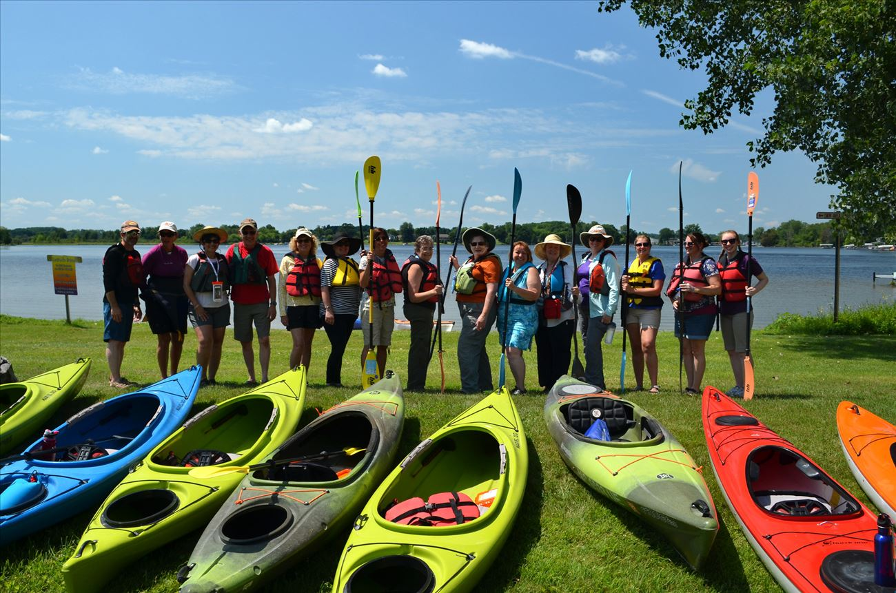 People standing behind kayaks with their flotation vests on and holding paddles